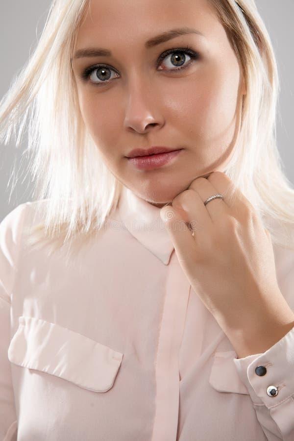 Mooi vrouwelijk blondemodel die in overhemd haar haar houden stock foto