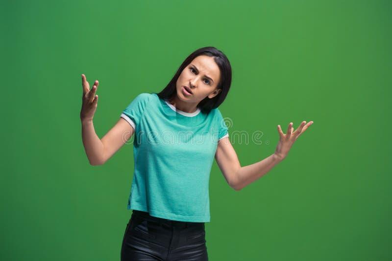 Mooi vrouwelijk die helft-lengte portret op groene studio wordt geïsoleerd backgroud De jonge emotionele verraste vrouw royalty-vrije stock fotografie