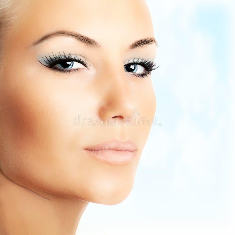 Mooi vrouwelijk gezicht over blauwe hemelachtergrond stock foto's
