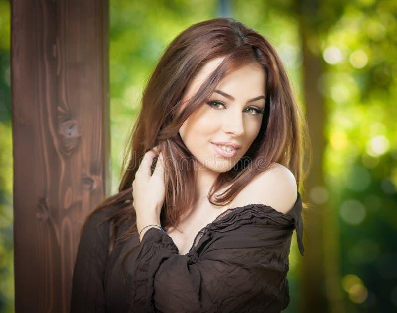 Mooi vrouwelijk portret met lang bruin haar openlucht Echt natuurlijk brunette met lang haar in park Aantrekkelijke vrouw stock foto