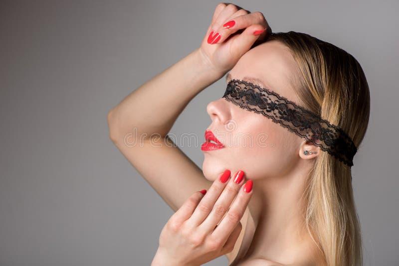 Mooi vrouwenblonde met kant op ogen over grijze achtergrond stock afbeeldingen