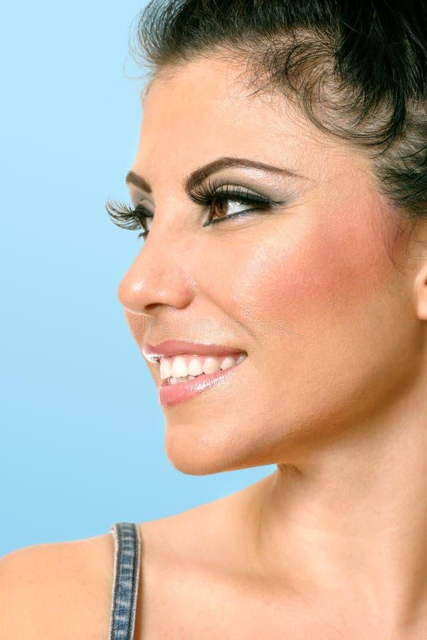 Mooi vrouwengezicht dat zijdelings eruit ziet stock foto