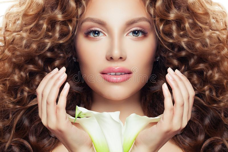 Mooi vrouwengezicht Het perfecte modelmeisje met lang krullend haar, de duidelijke huid en de lelie bloeien royalty-vrije stock fotografie