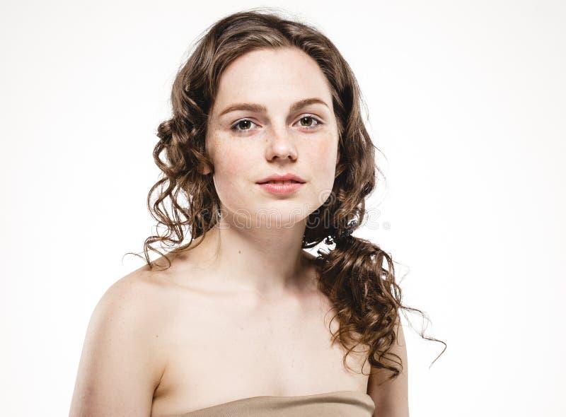 Mooi vrouwengezicht met krullende vliegende haarstudio op wit stock fotografie