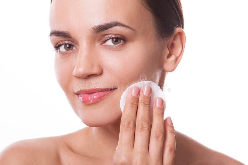 Mooi vrouwenmeisje die haar gezicht met katoenen stootkussenvezel reinigen stock foto