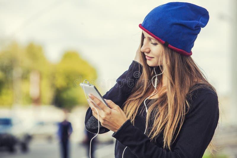 Mooi vrouwenmodel met telefoon en hoofdtelefoons op de straat royalty-vrije stock foto's