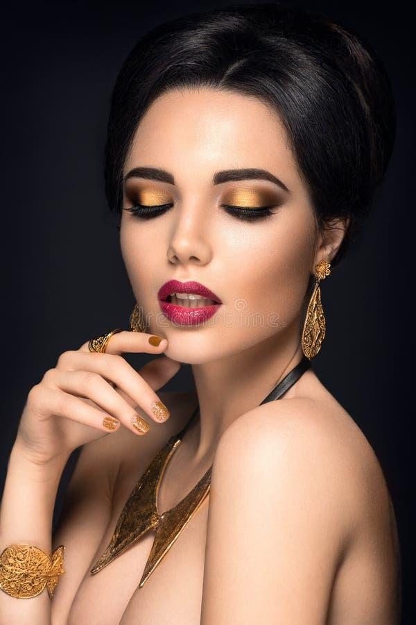 Mooi vrouwenportret Het jonge dame stellen met gouden juwelen royalty-vrije stock foto's
