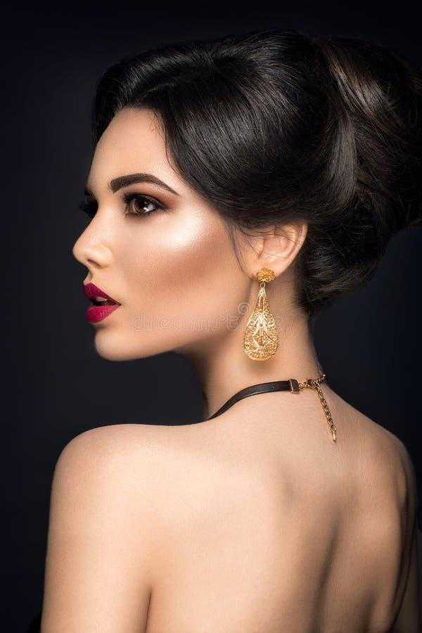 Mooi vrouwenportret Het jonge dame stellen met gouden juwelen stock afbeeldingen