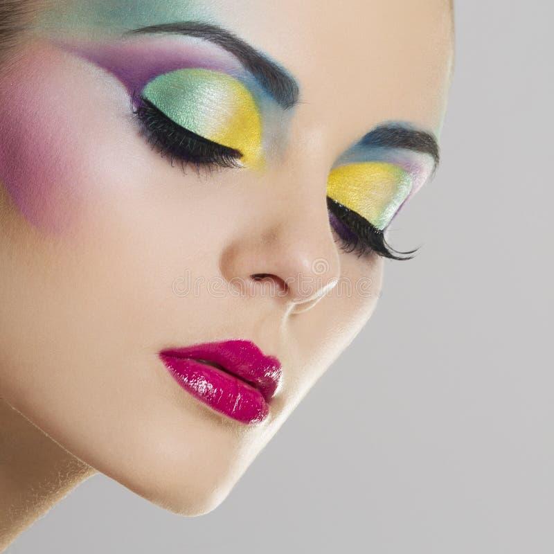 Mooi vrouwenportret met heldere kleurrijke make-up stock afbeelding