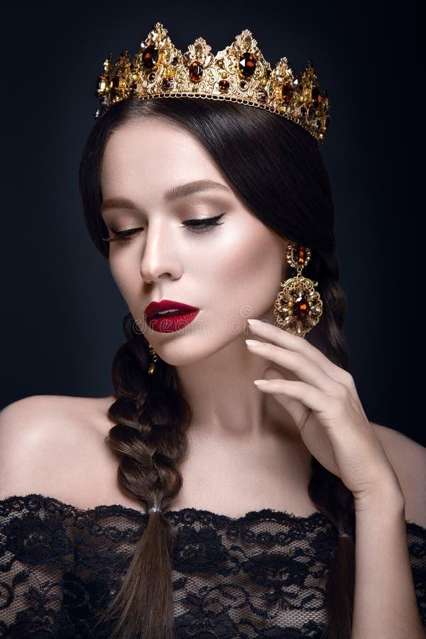 Mooi vrouwenportret met kroon en oorringen stock afbeeldingen