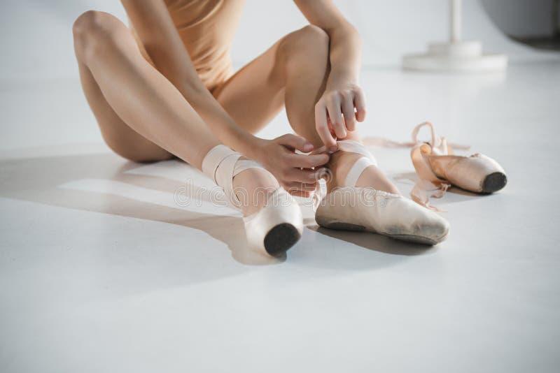 Mooi weinig ballerina die te voet pointe schoenen zetten royalty-vrije stock foto's