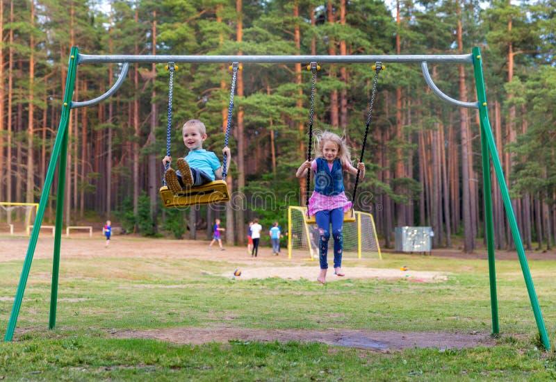 Mooi weinig blondemeisje en jongen die in openlucht op speelplaats slingeren royalty-vrije stock afbeelding