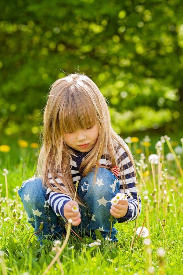 Mooi weinig blondemeisje, spelen openlucht, de lente royalty-vrije stock fotografie