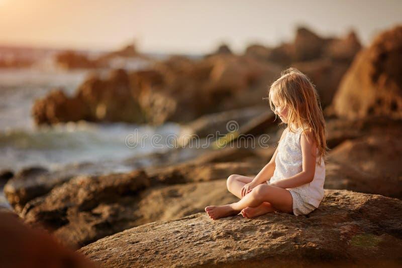 Mooi weinig engelen gir zitting op een rots en het onderzoeken van de afstand stock foto