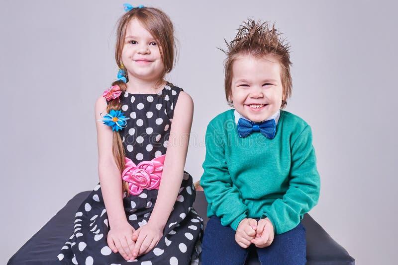 Mooi weinig jongen en meisje die, met grappige gelaatsuitdrukkingen glimlachen royalty-vrije stock foto's