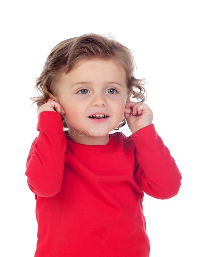 Mooi weinig kind twee jaar oud wat betreft zijn oren royalty-vrije stock foto
