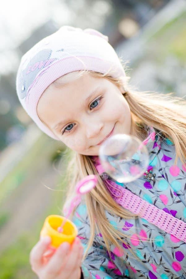 Mooi weinig leuk meisje met blauwe ogen die pret het gelukkige het glimlachen spelen hebben & het bekijken zeepbel op lente of de stock fotografie