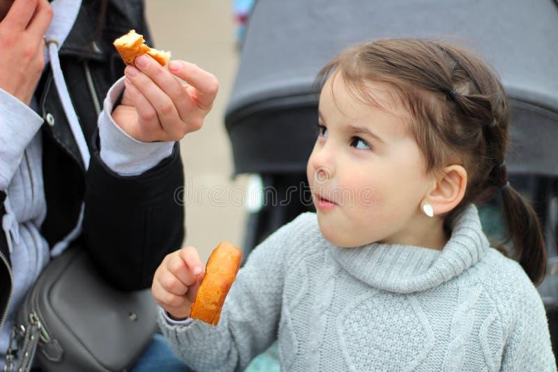mooi weinig vrolijk glimlachend meisje met haar moeder op een gang in de straat royalty-vrije stock fotografie