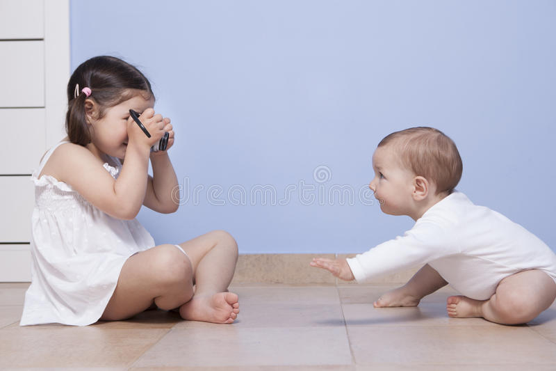 Mooi weinig zuster die beelden nemen aan haar babybroer royalty-vrije stock foto