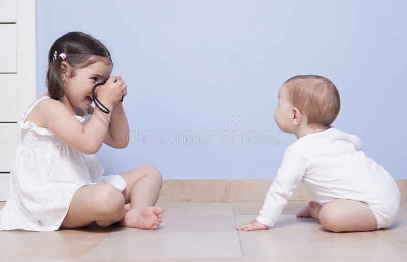 Mooi weinig zuster die beelden nemen aan haar babybroer royalty-vrije stock fotografie