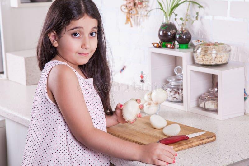 Mooi werkt weinig de 7 jaar van het Middenoosten oud meisjes met mes en ui in de witte keuken Het schot van de studio stock foto