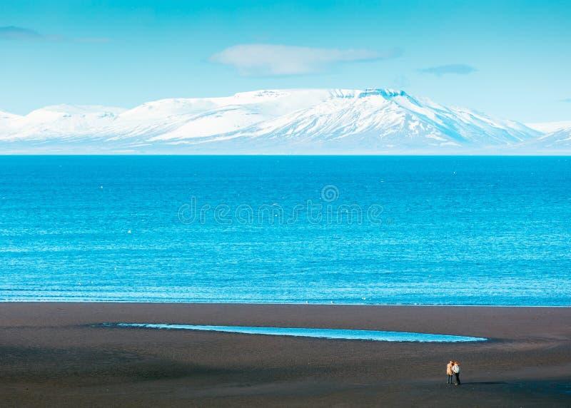 Mooi wijd geschoten van het overzees met verbazende witte berg op de achtergrond royalty-vrije stock fotografie