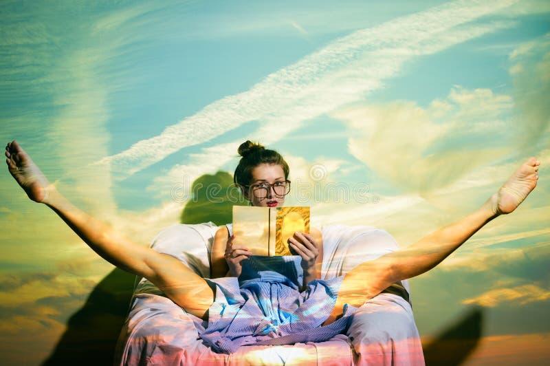 Mooi wijfje die een boekzitting als voorzitter lezen tegen de blauwe achtergrond van de hemelmuur royalty-vrije stock foto's