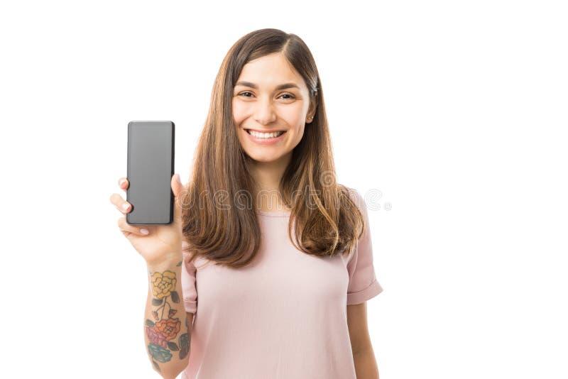 Mooi Wijfje die en Haar Nieuwe Mobiele Telefoon glimlachen voorstellen royalty-vrije stock afbeeldingen