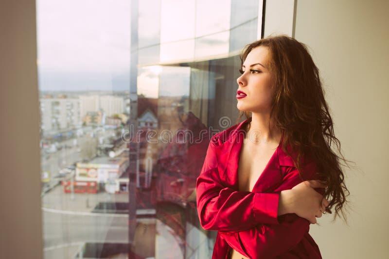Mooi wijfje die pret ontspannen hebben die uit het venster, portret kijken royalty-vrije stock afbeeldingen
