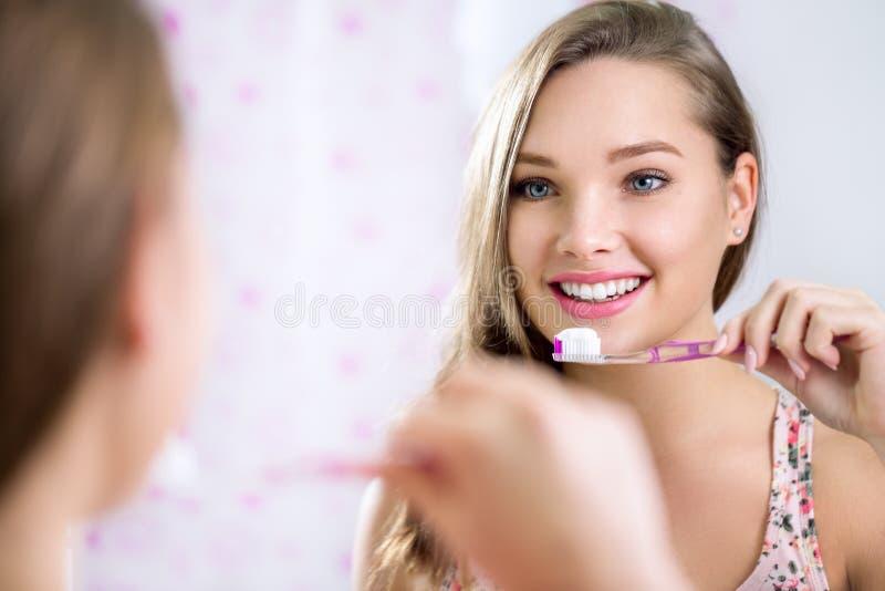 Mooi wijfje die in spiegel kijken terwijl het borstelen van tanden stock afbeelding