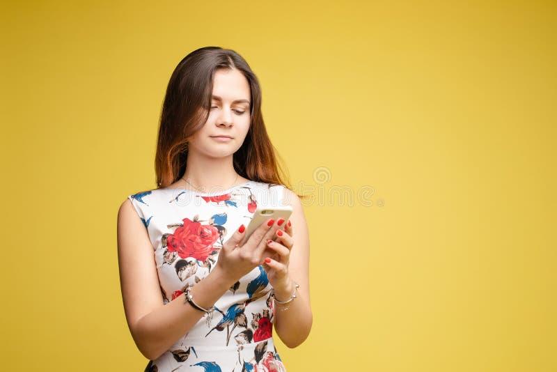 Mooi wijfje in heldere kleding die telefoon en het chattering houden stock afbeeldingen