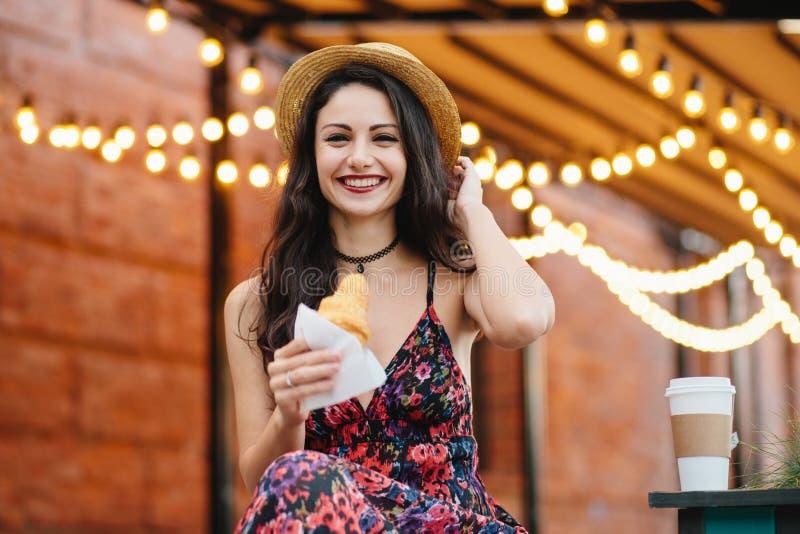 Mooi wijfje met donker haar, aantrekkelijke verschijning, die hoed, kleding en halsband dragen, die heerlijk croissant houden die stock fotografie