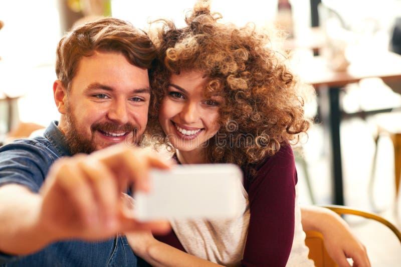 Mooi wijfje met mannetje die selfie maken stock afbeeldingen