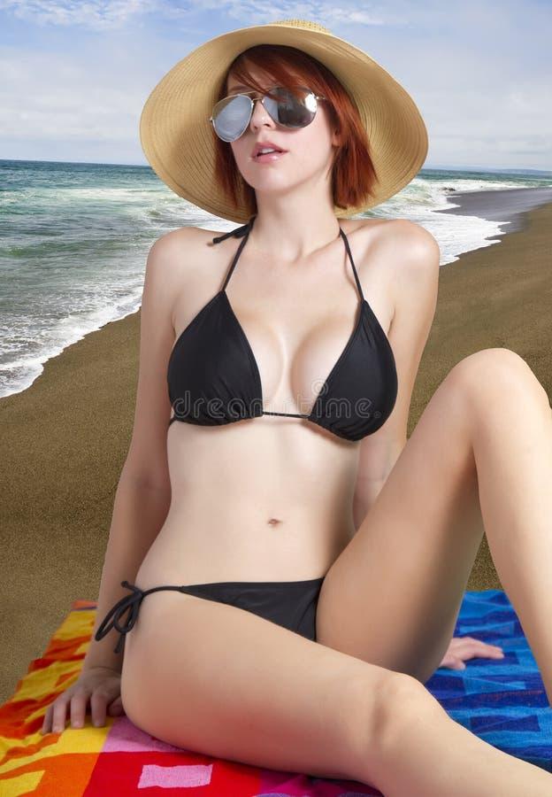 Mooi wijfje op het strand in zwarte bikini royalty-vrije stock foto's