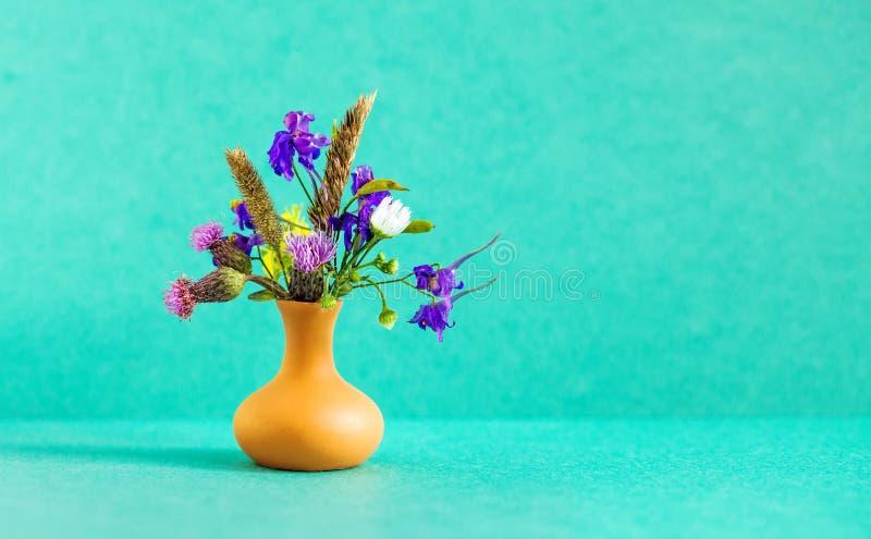 Mooi wild bloemenboeket, bruine kleivaas op groene achtergrond Floristische het stillevenfoto van de de zomertijd ondiep stock fotografie