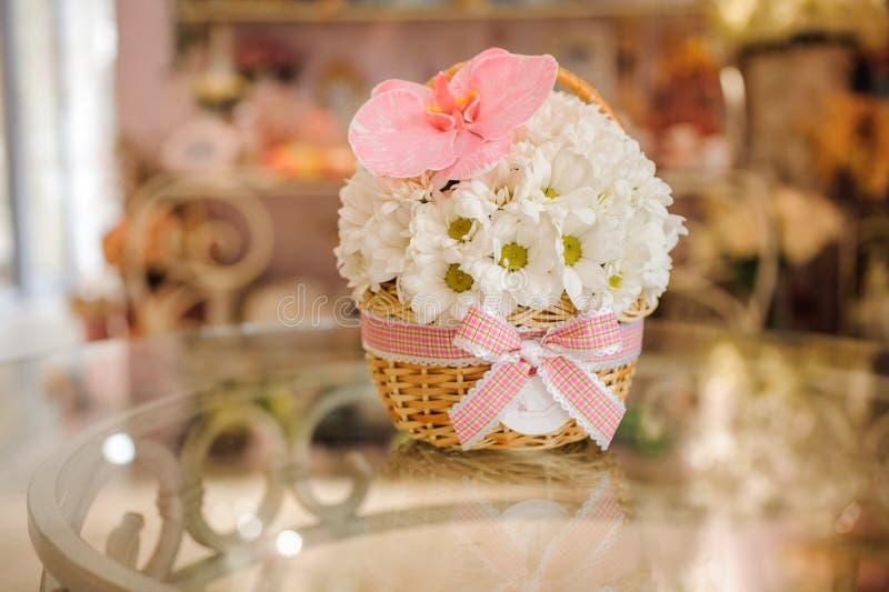 Mooi wit boeket van gemengde bloemen in mand op lijst stock foto