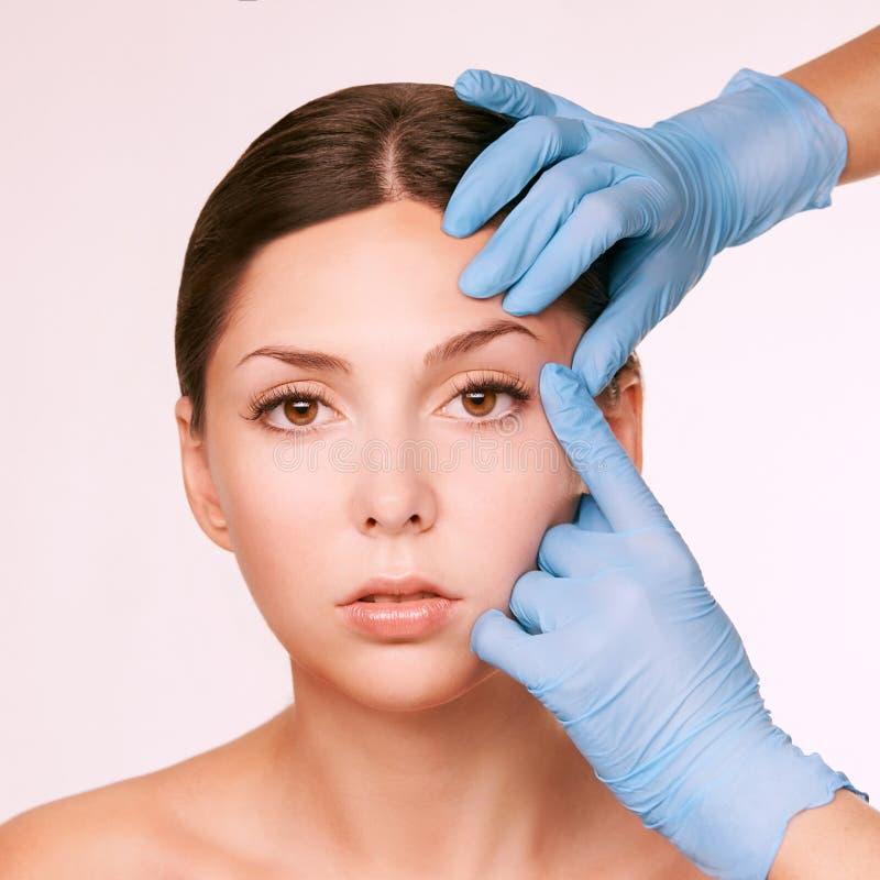 Mooi wit meisje Medische handschoenen dichtbij gezicht De kosmetiekprocedure royalty-vrije stock afbeelding
