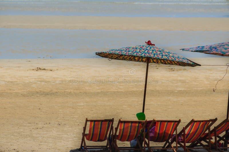 Mooi wit zandig strand met paraplu's en rij van stoelen stock foto