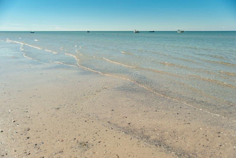 mooi zandig strand en zachte blauwe overzeese golf panorama van zeegezicht met blauwe hemel bij daglicht vissersboten op horizon stock foto