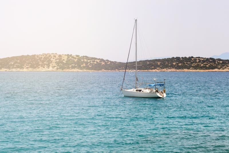 Mooi zeegezicht met wit varend jacht in het blauwe overzees Verminderde de zeilen, rust Het concept stagnatie, geen doel, dropp royalty-vrije stock foto's