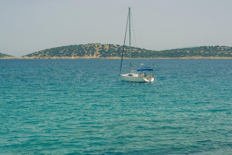 Mooi zeegezicht met wit varend jacht in het blauwe overzees Verminderde de zeilen, rust Het concept stagnatie, geen doel, dropp stock fotografie