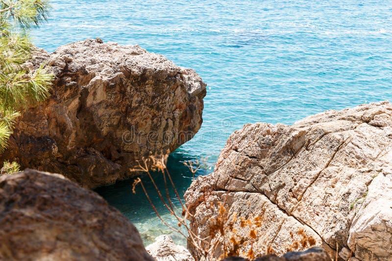 Mooi Zeegezicht Zeegezicht op de achtergrond van het wilde rotsachtige kust Wilde strand, het azuurblauwe water en de rotsen stock afbeelding