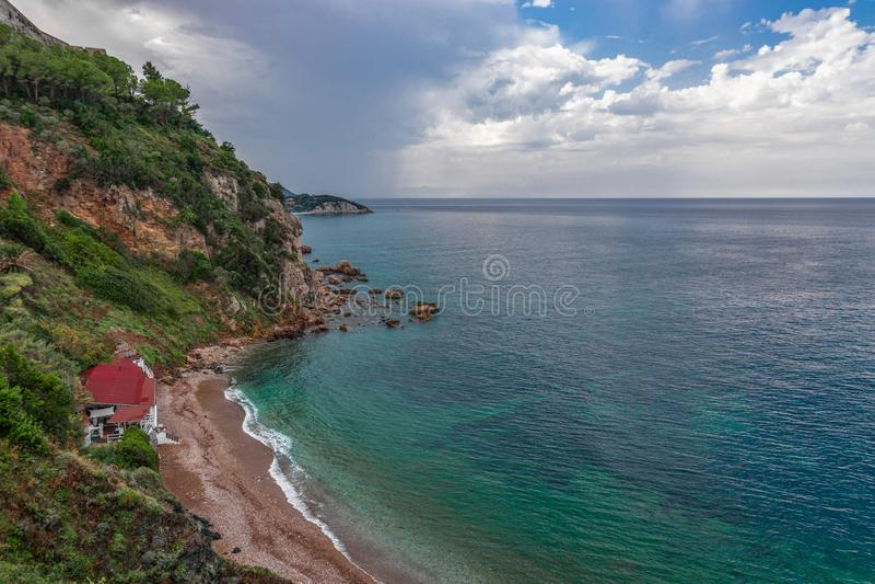 Mooi zeegezicht van de rotsachtige kust en een klein strand met een restaurant Bewolkte hemel na regen en smaragdgroene wateren v royalty-vrije stock foto