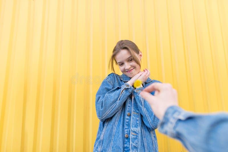 Mooi zich op een achtergrond van gele muur bevinden en meisje die gelukkig op een bloem in de handen van de mens kijken stock afbeeldingen