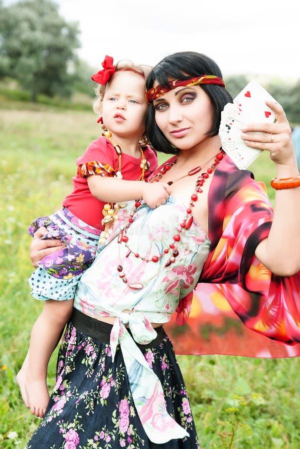 Mooi zigeunermeisje in een rode kleding met de baby royalty-vrije stock afbeeldingen