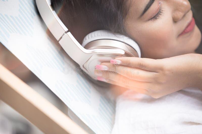 Mooi zij de schoonheidsconcept van de meisjes ontspannend pool de gelukkige meisjesglimlach anf luistert aan muziek met hoofdtele stock foto's