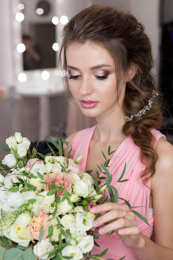 Mooi zoet voor het huwelijk van een vriend in de roze avondjurk met avondkapsel voorbereidingen treffen en helder meisjesbruidsme stock fotografie