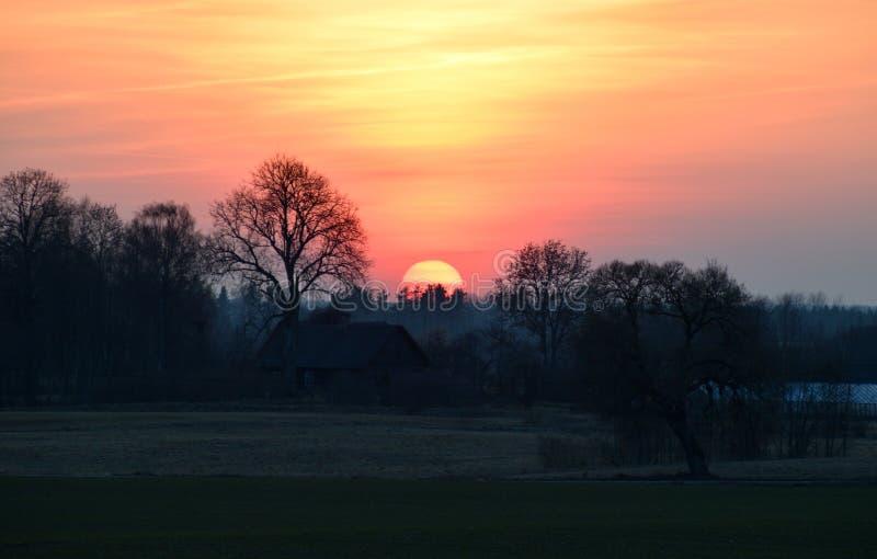 Mooi zonsonderganglandschap met een huis Letland, Vidzeme stock afbeelding