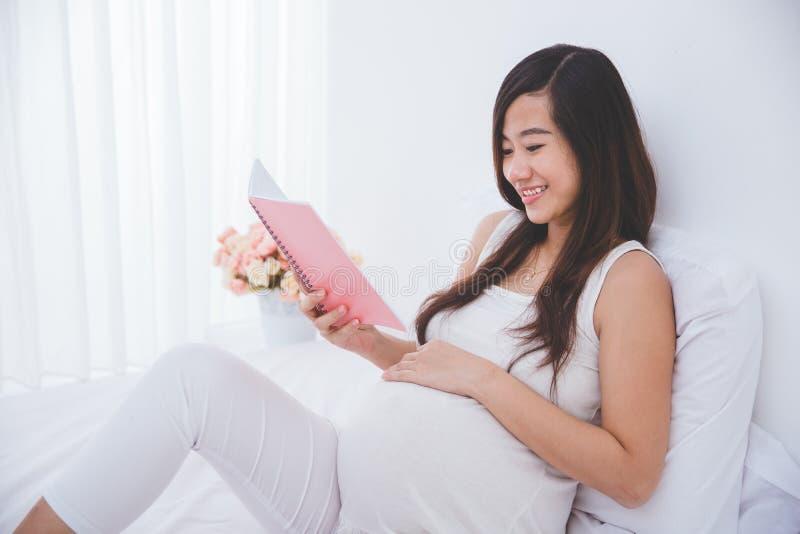 Mooi zwanger Aziatisch de notaboek van de vrouwenlezing, het glimlachen stock foto