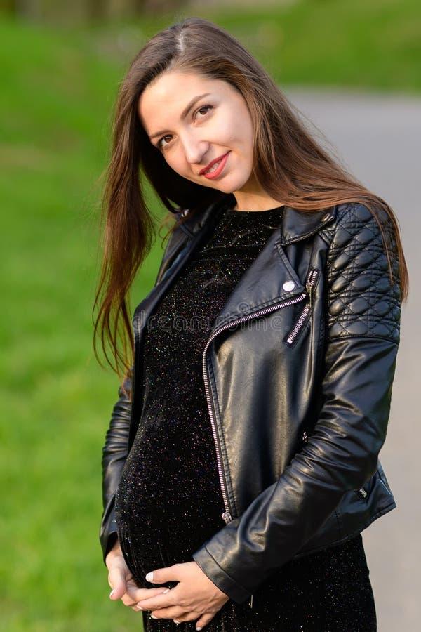 Mooi zwanger brunette Mooie zwangere vrouw Schitterend zwanger meisje in openlucht Brunette met lange gelukkige haardame - stock foto